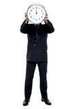 Reloj de pared ejecutivo del soporte delante de su cara Imágenes de archivo libres de regalías