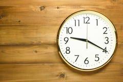 Reloj de pared en la pared de madera Imagenes de archivo