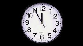 Reloj de pared en un 23:55 del fondo del negro almacen de video
