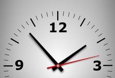 Reloj de pared en un fondo gris Fotografía de archivo