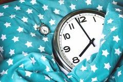 Reloj de pared grande en una cama y un despertador azules fotos de archivo libres de regalías