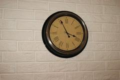 Reloj de pared redondo en textura ligera del ladrillo Fotos de archivo