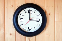 Reloj de pared redondo grande aislado en la pared de madera Imagen de archivo libre de regalías