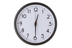 Reloj de pared redondo de la oficina en el blanco, mitad más allá de doce foto de archivo libre de regalías