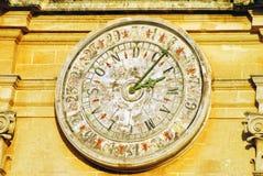 Reloj de pared viejo con el dial numérico y alfabético en un edificio en Mdina, Malta foto de archivo