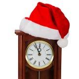 Reloj de pared y casquillo de Santa Claus, aislados en el fondo blanco Foto de archivo libre de regalías
