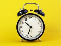 Reloj de tabla clásico en un fondo amarillo Fotografía de archivo