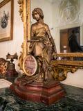 Reloj de tabla viejo con la estatua de oro de una figura femenina Fotografía de archivo libre de regalías