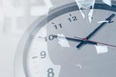 Reloj de tiempo con el hombre de negocios por horas de trabajo foto de archivo