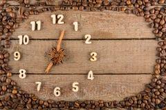 Reloj decorativo con números de madera y flechas hechas de los palillos de canela, mostrando las 7, en un fondo de madera y un ma fotos de archivo