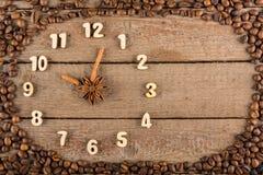 Reloj decorativo con números de madera y flechas hechas de los palillos de canela, mostrando las 10, en un fondo de madera y un m fotos de archivo