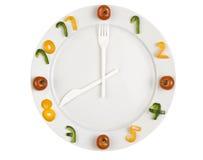 Reloj del alimento en el fondo blanco Imagenes de archivo