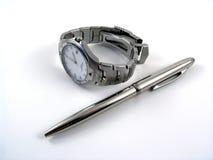 Reloj del asunto cerca de una pluma de bola de plata Imágenes de archivo libres de regalías