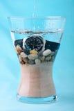 Reloj del equipo de submarinismo en un florero con la arena y los guijarros Imagen de archivo libre de regalías