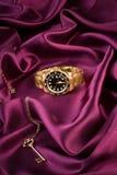 Reloj del oro que miente en el paño de seda Foto de archivo libre de regalías