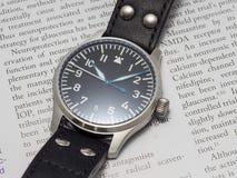 Reloj del piloto de Stowa con el fondo del diario Fotografía de archivo libre de regalías