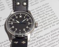 Reloj del piloto de Stowa con el fondo del diario Imagen de archivo