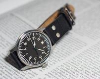 Reloj del piloto de Stowa con el fondo del diario Imágenes de archivo libres de regalías