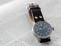Reloj del piloto de Stowa con el fondo del diario Fotos de archivo