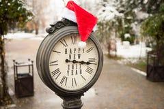 Reloj del vintage con el sombrero de santa y la Feliz Año Nuevo de las palabras Fotos de archivo libres de regalías
