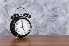 reloj del vintage del reloj del ` de 5 o en el fondo de madera de la tabla y de la pared Fotografía de archivo