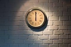 Reloj del vintage en una pared de ladrillo blanca Imágenes de archivo libres de regalías