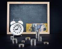 Reloj del vintage, pizarra, 50 dólares de cuenta australianos, y moneda Fotografía de archivo libre de regalías