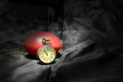 Reloj del vintage y corazón rojo en fondo negro, concepto del amor y del tiempo en fotografía inmóvil de la vida Foto de archivo