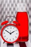 Reloj del vintage y garrafa rojos del vino Foto de archivo libre de regalías