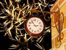 Reloj del vintage y pared de ladrillo amarilla en fondo de oro del fuego artificial imágenes de archivo libres de regalías