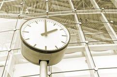 Reloj delante de un edificio de oficinas foto de archivo