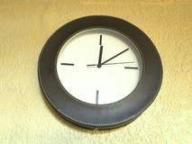 reloj elegante, colgando en la pared del beige Foto de archivo libre de regalías