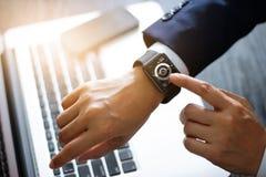 Reloj elegante conmovedor de las manos del hombre de negocios Usando un mercado de acción app y gráfico en la pantalla virtual mo Imagen de archivo
