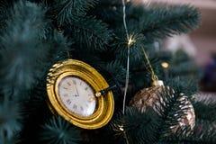 Reloj en el árbol de navidad con las luces Fotos de archivo libres de regalías