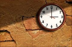 Reloj en el cemento viejo de la pared. Imagen de archivo