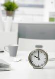 Reloj en el escritorio de oficina Imagen de archivo