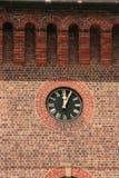 Reloj en la pared de ladrillo Foto de archivo libre de regalías