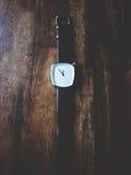 Reloj en la tabla de madera imagenes de archivo
