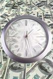 Reloj en los 100 billetes de banco del dólar Fotografía de archivo libre de regalías