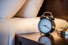 Reloj en sitio de la cama Foto de archivo