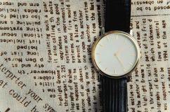Reloj en un fondo de la materia textil Foto de archivo