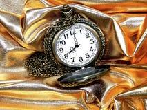 Reloj en un fondo del oro Imágenes de archivo libres de regalías