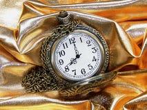 Reloj en un fondo del oro Fotos de archivo