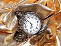 Reloj en un fondo del oro Fotografía de archivo