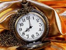 Reloj en un fondo del oro Imagen de archivo libre de regalías