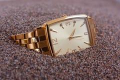 Reloj enterrado en arenas Foto de archivo libre de regalías