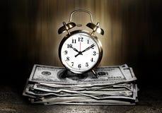 Reloj gemelo de la alarma en el dinero Fotos de archivo libres de regalías