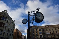 Reloj hermoso y termómetro análogo con los edificios hermosos detrás del cuadrado de la catedral en León Arquitectura, viaje, his imagen de archivo libre de regalías
