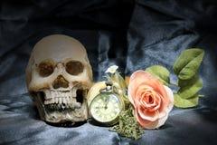 Reloj humano del cráneo y de bolsillo del vintage con el corazón y flor en el fondo, el amor y el tiempo negros, aún fotografía d Foto de archivo