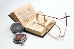 Reloj, libro y vidrios de bolsillo Fotografía de archivo
